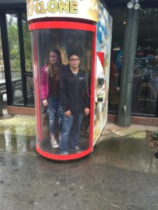 Emily and Saej are blasted with air in the Cyclone wind simulator.